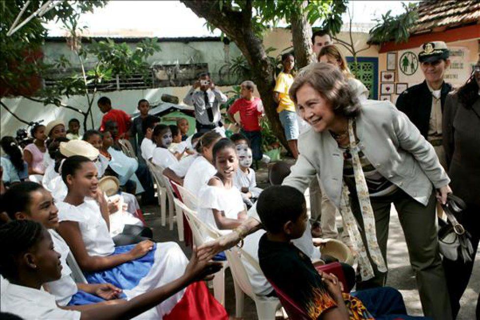 Doña Sofía saluda a unos niños durante su visita a la ONG española Paideia